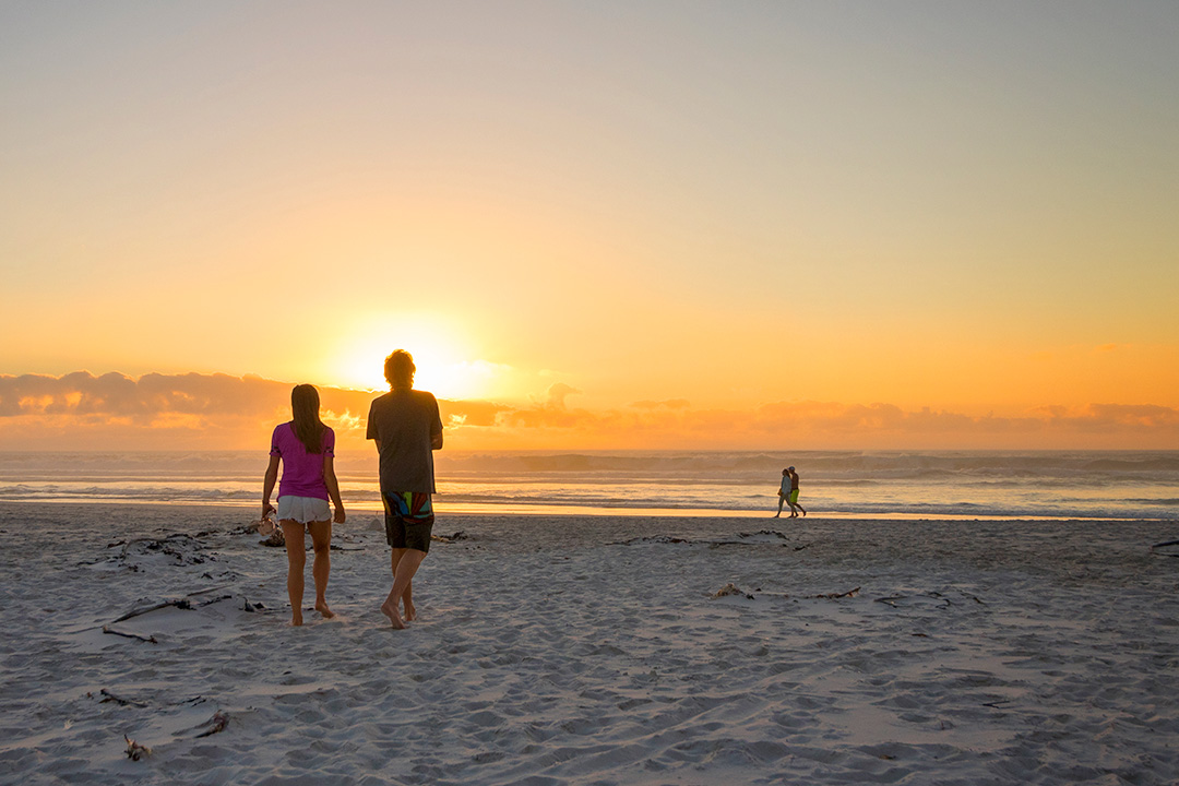 Man and woman take romantic sunset walk on Noordhoek Beach